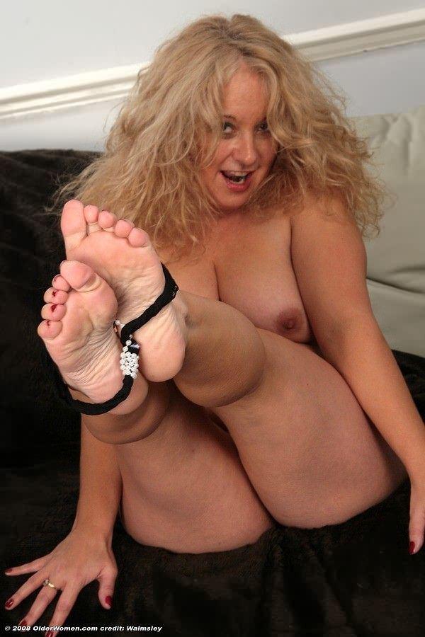 Mature fume les pieds nus dans le salon.